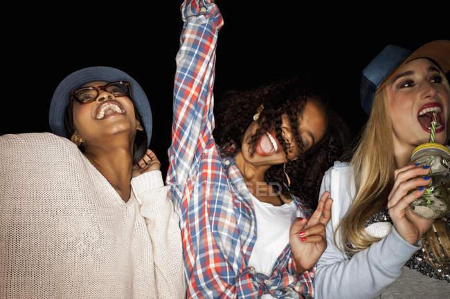 Giovani donne fianco a fianco braccia alzate sorridenti — Foto stock