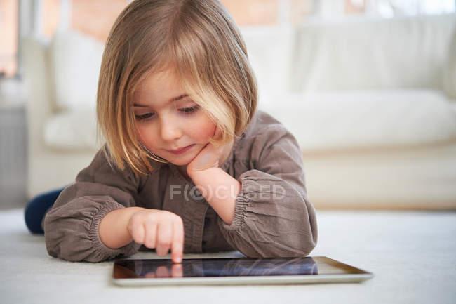 Menina deitada no chão usando tablet digital — Fotografia de Stock