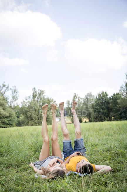Молодая пара лежит на траве в поле, ноги подняты — стоковое фото