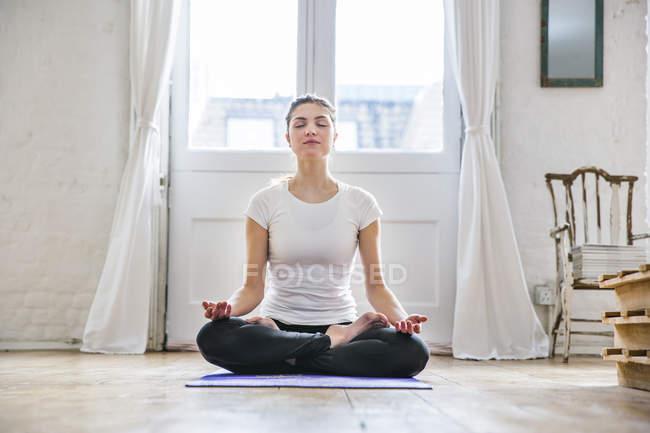Junge Frau praktizieren Yoga Lotus-Position in Wohnung — Stockfoto