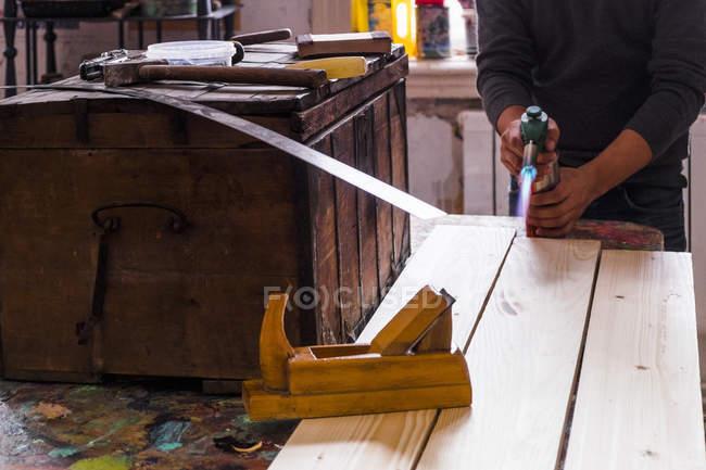 Partie médiane de l'homme adulte moyen utilisant une torche soufflée sur une planche de bois — Photo de stock