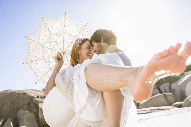 Man carrying woman holding lace umbrella in arms face to face smiling — Stock Photo