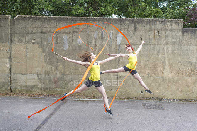 Young women practising ribbon dance on court — Stock Photo