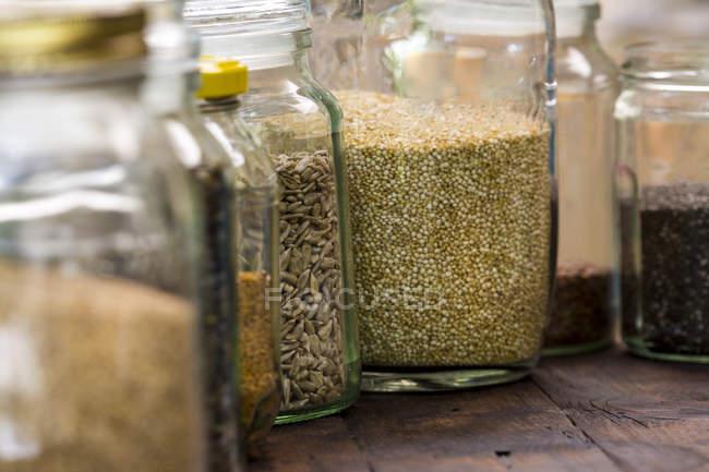 Vasetti di quinoa, girasole e semi di lino sul tavolo — Foto stock