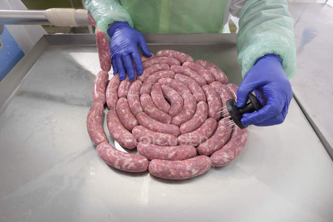Worker making Italian sausages in factory — Stock Photo
