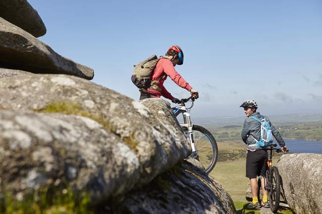 Cyclistes avec des vélos sur l'éperon rocheux — Photo de stock