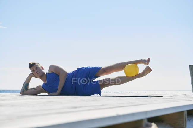 Man on pier lying on side resting on elbow, ball between legs — Stock Photo