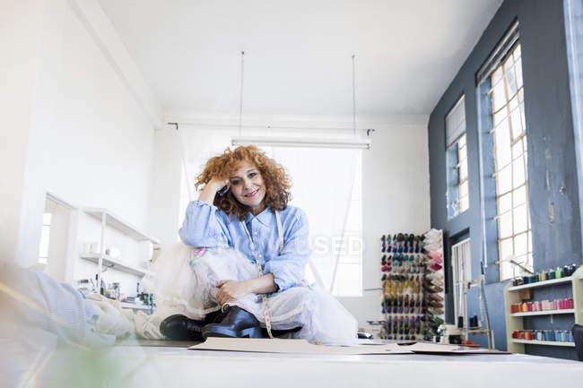 Fashion designer sitting cross-legged on desk looking at camera smiling — Stock Photo