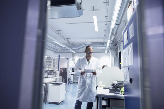 Lab assistant checking detail on digital tablet — Stock Photo