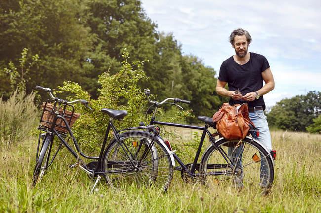 Ciclista masculino desempacotando Holdall no campo rural — Fotografia de Stock
