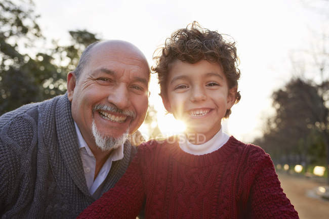 Portrait of grandfather and grandson looking at camera smiling — Stock Photo