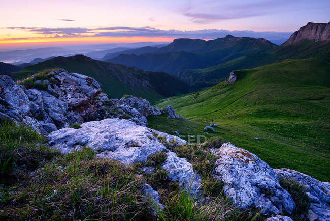Landscape with green hills at dusk with cloudy sky — Stock Photo