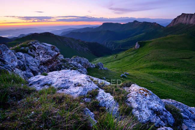 Landschaft mit grünen Hügeln in der Abenddämmerung mit bewölktem Himmel — Stockfoto