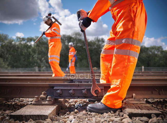 Railway workers wearing high visibility clothing repairing railway track side view — Stock Photo