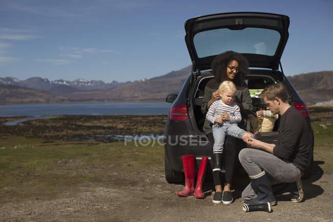 Genitori che aiutano il figlio a cambiare scarpe, Loch Eishort, Isola di Skye, Ebridi, Scozia — Foto stock