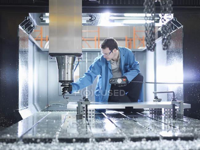 Travailleur dans une grande machine CNC dans une usine de plastique — Photo de stock