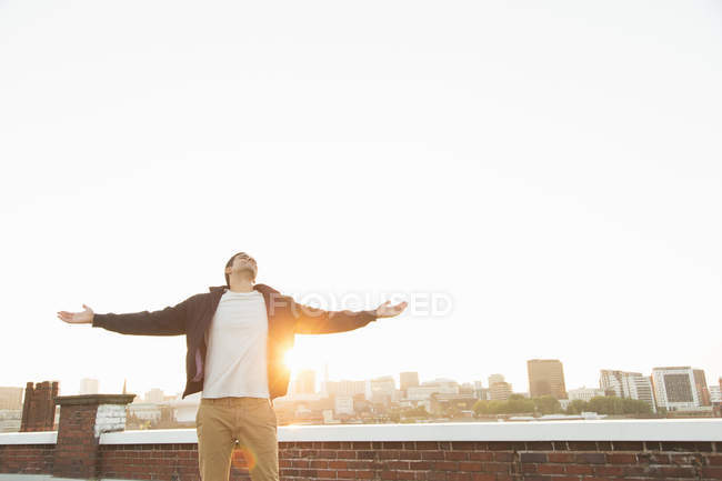 Man on rooftop with arms outstretched — Stock Photo