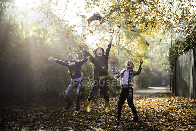 Three young boys, playing outdoors, throwing autumn leaves — Stock Photo