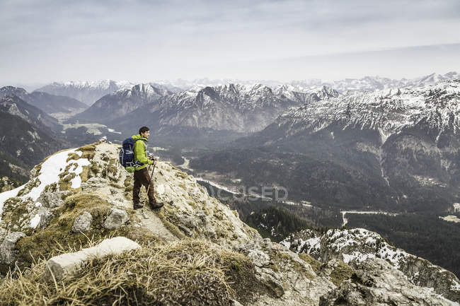 Young male hiker looking at view from Klammspitze mountain, Oberammergau, Bavaria, Germany — Stock Photo