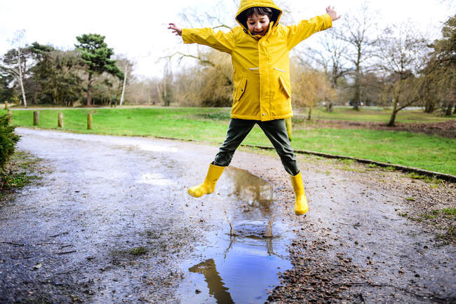Boy in yellow anorak jumping above puddle in park — Stock Photo