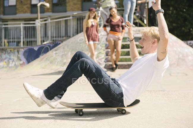 Young male skateboarder sitting on skateboard on the move in city skatepark — Stock Photo