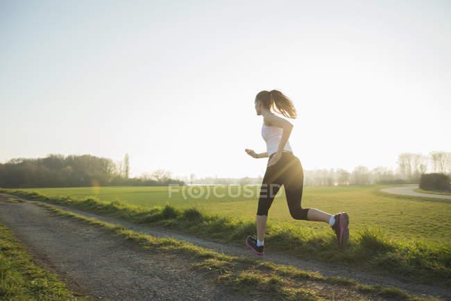 Jeune coureuse sur piste de terre — Photo de stock