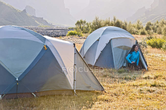 Woman looking out of tent at campsite Basar, Thorsmork, South Iceland, Iceland - foto de stock