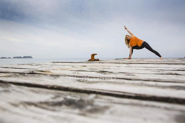 Mitte erwachsene Frau übt Yogaposition auf hölzernem Seebrücke — Stockfoto