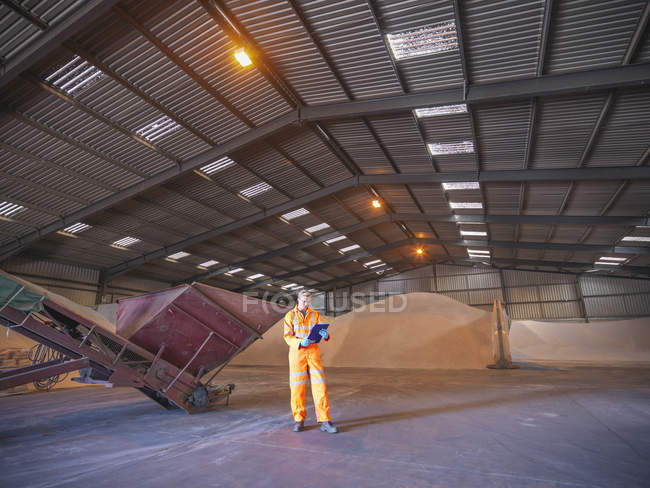 Worker checking clipboard in warehouse with zircon sand — Stock Photo