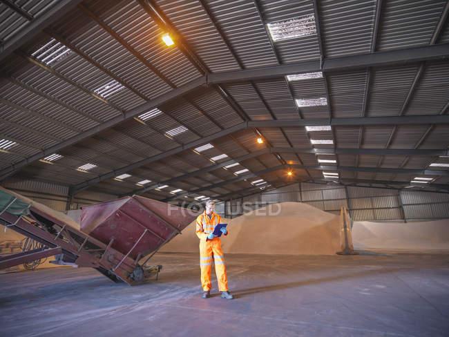 Рабочий проверяет буфер обмена на складе с цирконовым песком — стоковое фото