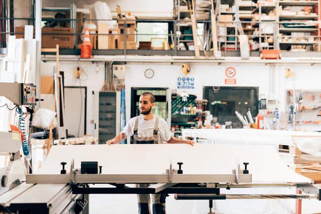 Jeune menuisier adulte au travail en atelier — Photo de stock