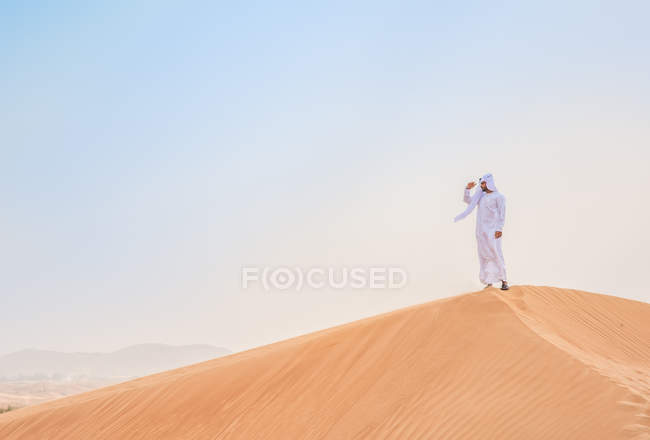 Middle eastern man wearing traditional clothes looking out from desert dune, Dubai, United Arab Emirates — Stock Photo