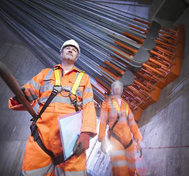 Retrato de engenheiros em frente à ancoragem por cabo em ponte suspensa, East Yorkshire, Reino Unido — Fotografia de Stock