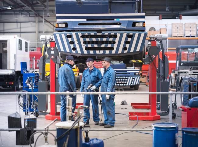 Інженери в обговоренні в авторемонтної фабрики — стокове фото