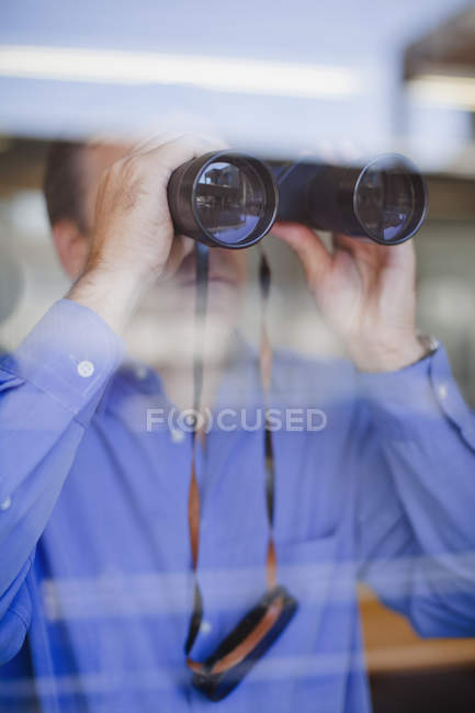 Бизнесмен смотрит через бинокль — стоковое фото