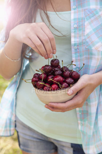 Cropped image of young woman with bowl of cherries — Stock Photo