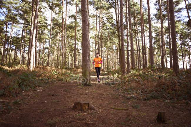 Femme mûre courant à travers une forêt — Photo de stock