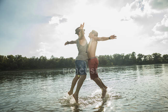 Young men chest bumping in lake — Stock Photo