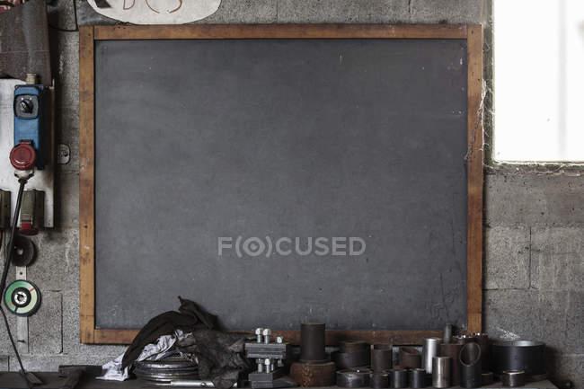 Blank blackboard, tools and tubes in workshop — Stock Photo
