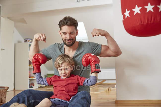 Хлопчик носить бокс з батьком, згинання м'язи дивляться на камеру — стокове фото