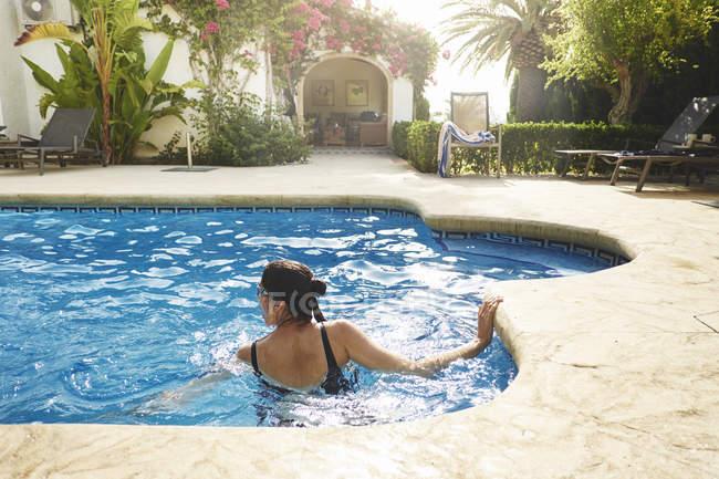 Femme mûre nageant dans un appartement de vacances piscine — Photo de stock