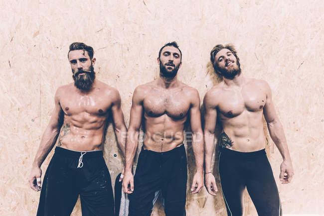 Портрет трех мачо кросс-тренеров в тренажерном зале — стоковое фото