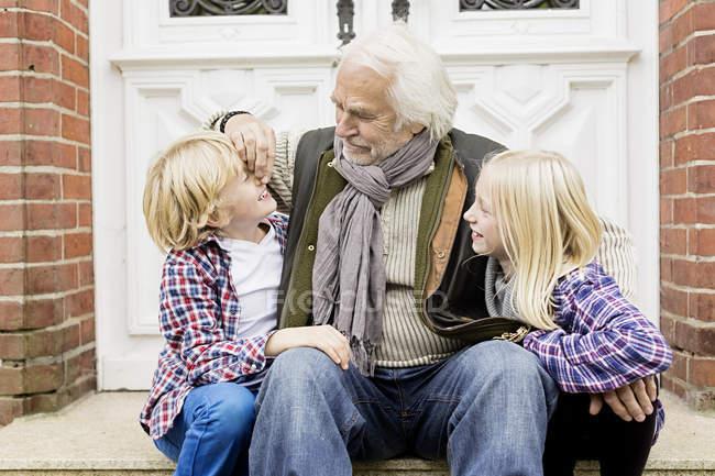 Nonno seduto con i nipoti sulla soglia di casa — Foto stock