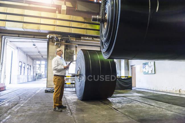 Чоловічий працівник оцінки рулон гуми в гумовому Роликовий завод — стокове фото