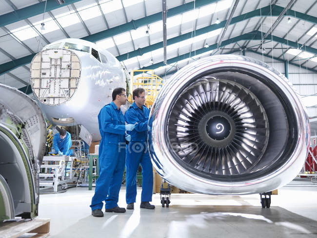 Engineers working on engine in aircraft maintenance factory — Stock Photo