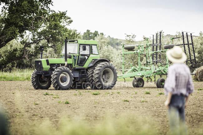 Adolescent, je regarde la conduite tracteur de charrue agriculteur dans le champ labouré — Photo de stock