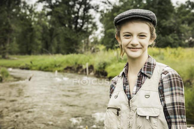 Muchacha con el casquillo plano por río sonriendo - foto de stock