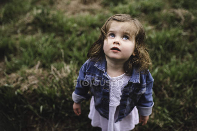 Portrait of young girl standing in field — Stock Photo