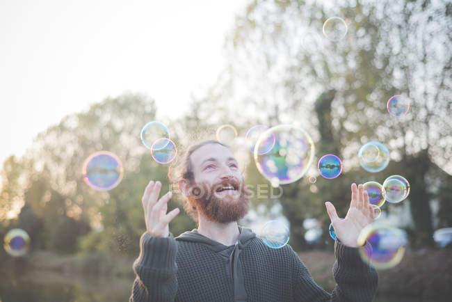 Молодой человек играет с пузырьками — стоковое фото