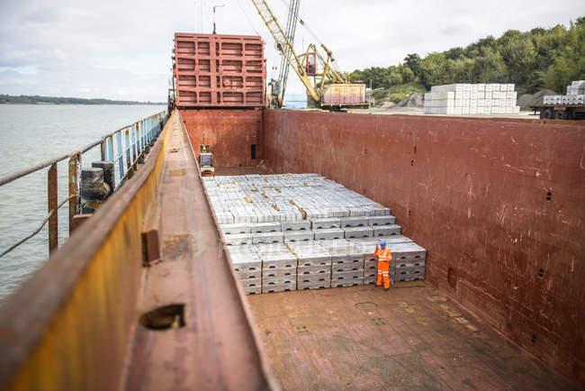 Operaio che controlla lingotti metallici nella stiva della nave — Foto stock